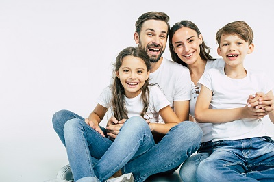 Happy beautiful and smiling dad, mommy and them kids sitting on the floor in white background