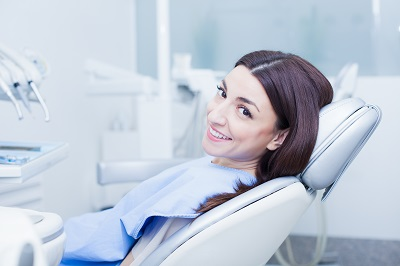 Image of smiling patient looking at camera at the dentist chair