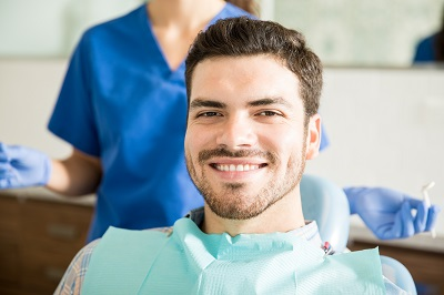 Portrait of relaxed smiling adult man in dental chair about to get treatment