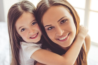 Beautiful young woman and her charming little daughter are hugging, looking at camera and smiling