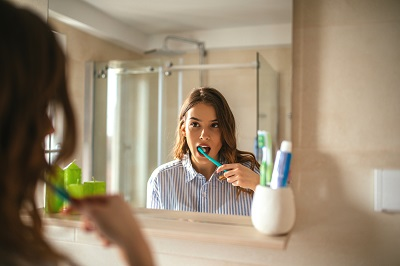 Portrait of a beautiful woman brushing teeth and looking in the mirror in the bathroom
