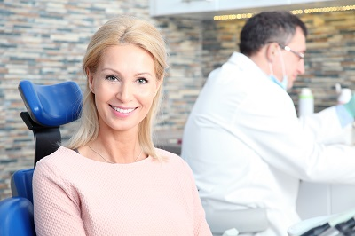 Portrait of beautiful middle age woman sitting at dental chair waiting for treatment