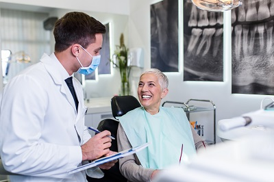 senior woman consulting dental implants with dental professional