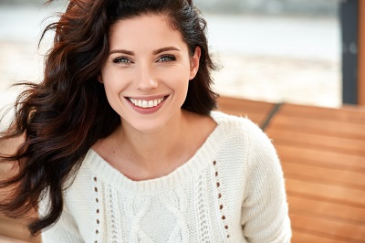 photo of brunette wearing patterned sweater smiling outdoors