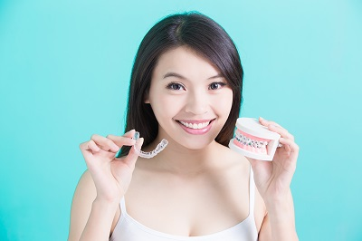 young woman holding invisalign clear braces and traditional braces