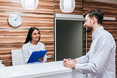 patient standing at reception desk