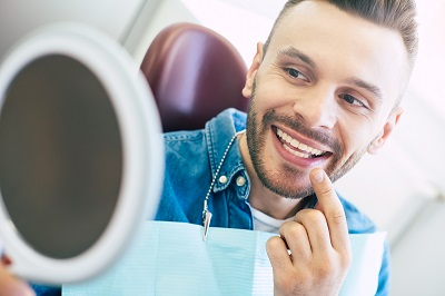 young man looking at his smile using mirror in dental office