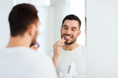 smiling young man with toothbrush cleaning teeth and looking to mirror at home bathroom