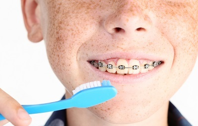 young boy with braces brushing teeth