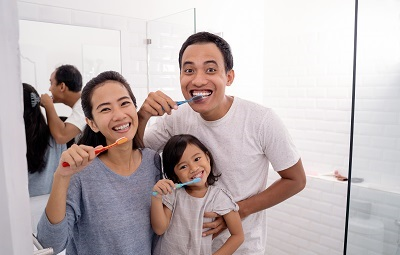 Portrait of happy family brushing their teeth together at home
