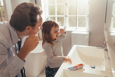 Father and daughter brushing teeth standing in bathroom