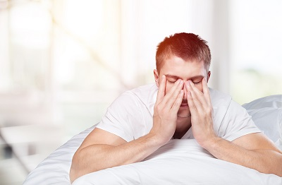 Young man laying in bed with hands on face at bedroom