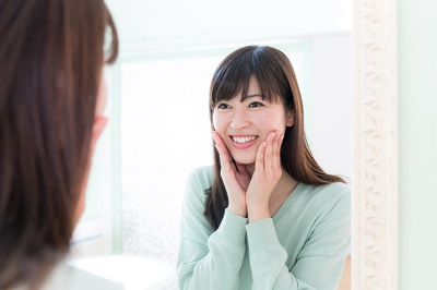 asian woman looking at her smile on the bathroom mirror
