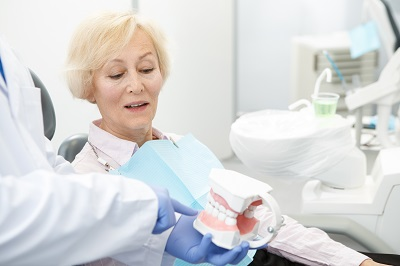 dental professional pointing at tooth model to explain dental procedure to senior woman patient
