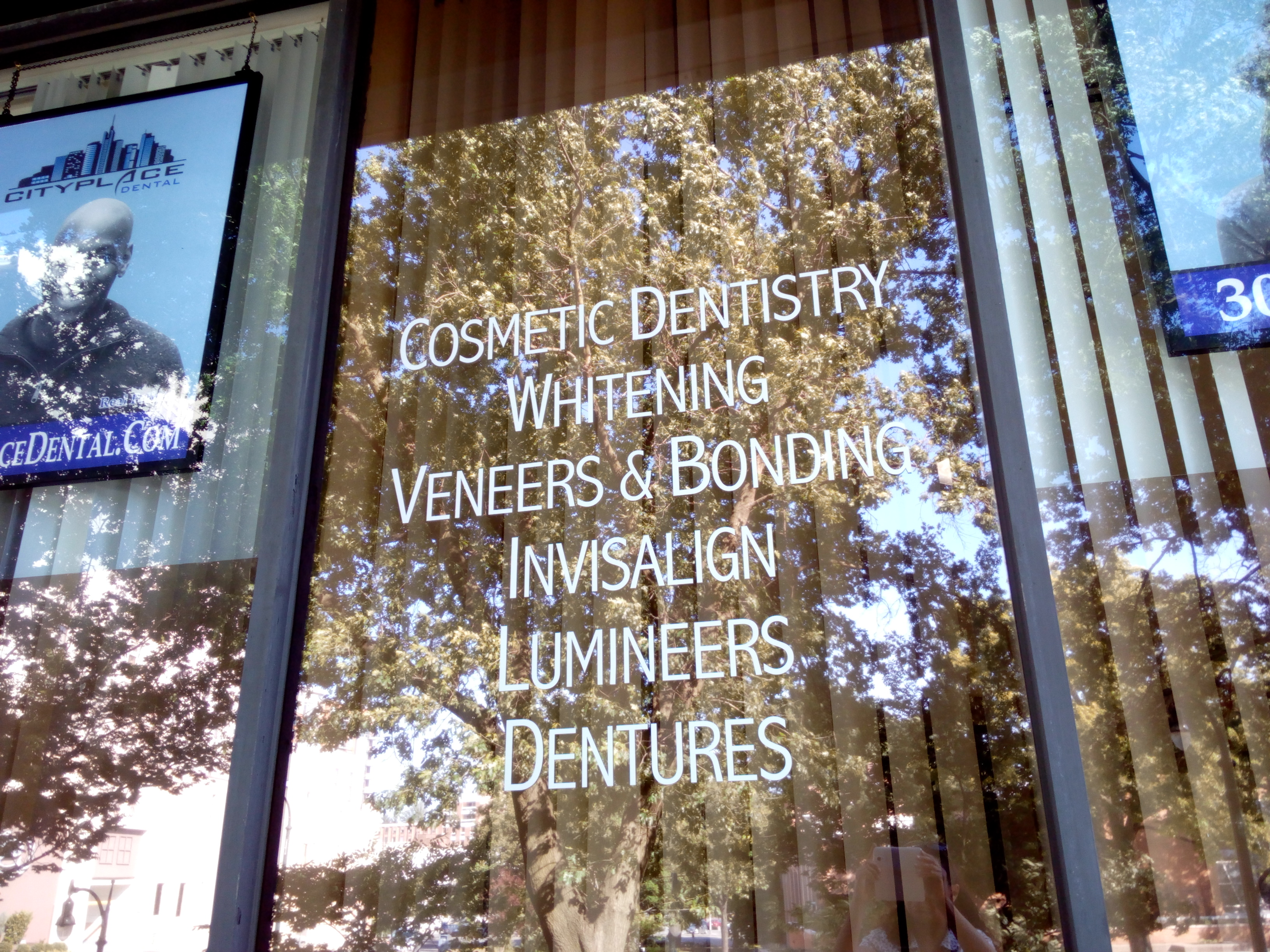 City Place Dental Procedures - Exterior dental office window with names of dental procedures.