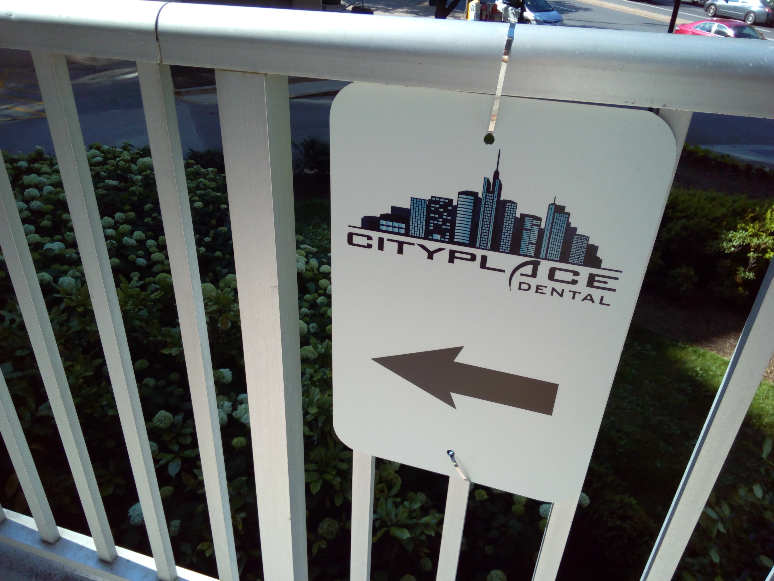 City Place Dental- Image of a sign for the dental office on a fence