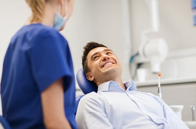 smiling male patient sitting in dental chair