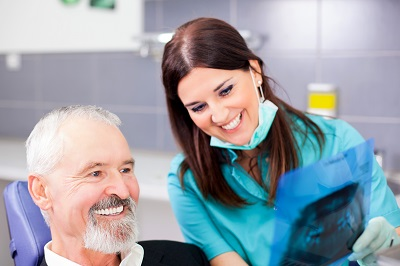 senior man looking at dental x-ray in dental office