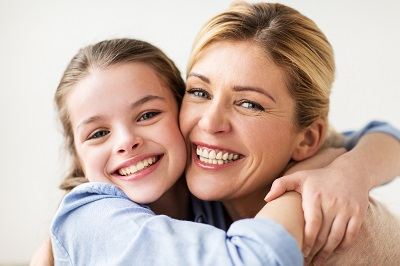 happy smiling girl with mother hugging