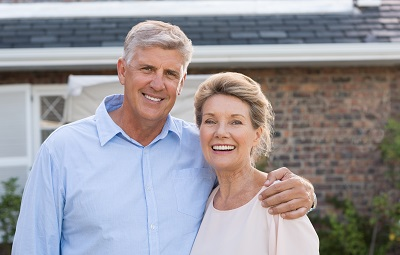 Portrait of a happy senior couple smiling in front of their house
