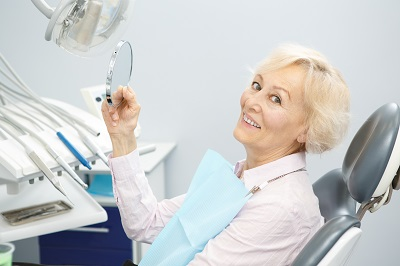 Image of senior woman checking out her smile with mirror in dental office