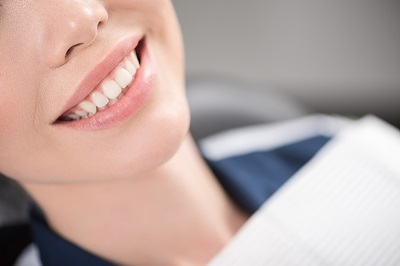 Image of close up of woman smiling while sitting in dental chair
