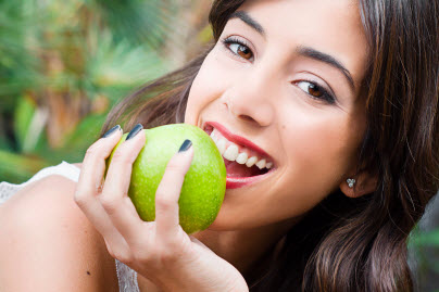 Girl smiling as she pretends to bite into green apple