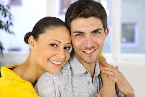 Woman hugging man from behind as they both smile