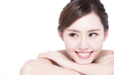 close up of asian woman smiling over white background