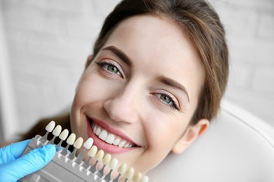 Young woman choosing color of teeth for veneer treatment at dentist