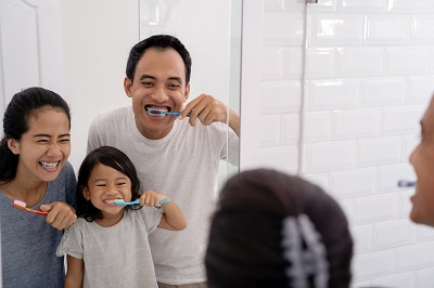 parents brushing teeth with daughter at home