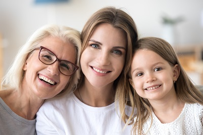 smiling grandmother, grown young daughter and child girl looking at camera