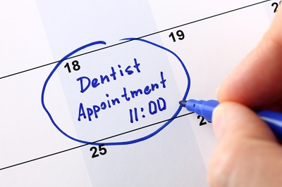 hand writing a reminder for a dentist appointment on calendar