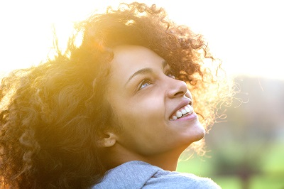 Close up portrait of a beautiful young african american woman smiling and looking up outdoors