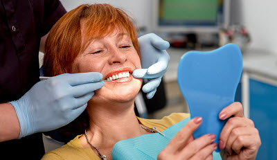 senior woman checking out her new smile in dental office