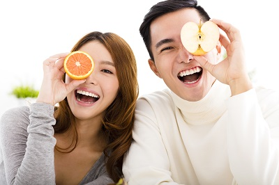 young happy couple holding half an apple and half an orange.