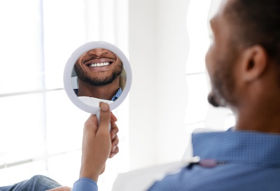 male patient checking out his smile with a mirror in dental office