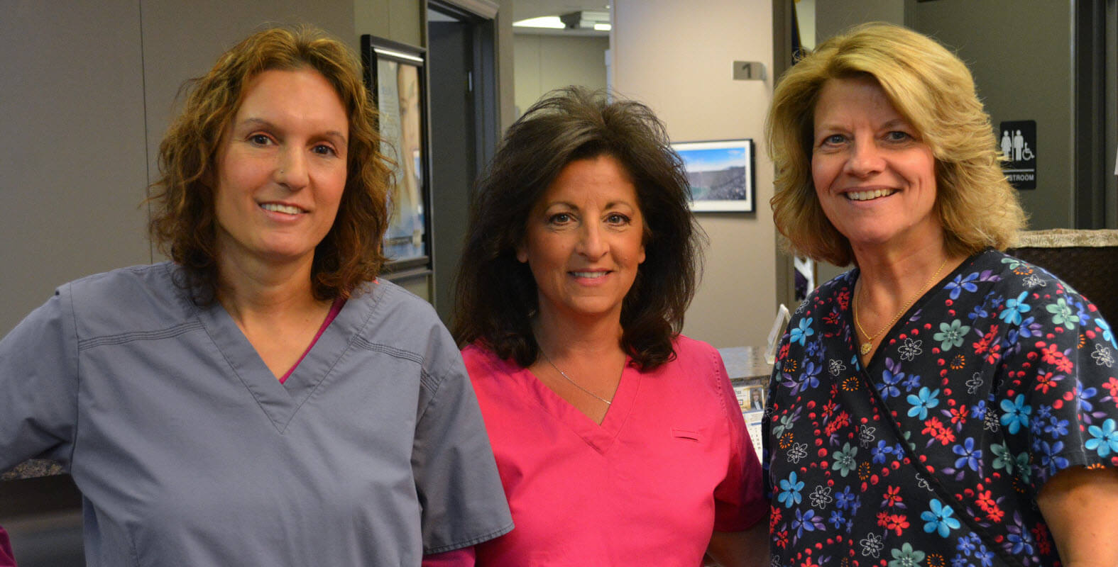 Three smiling women in scrubs
