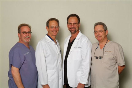 Four male dentists smiling in a group