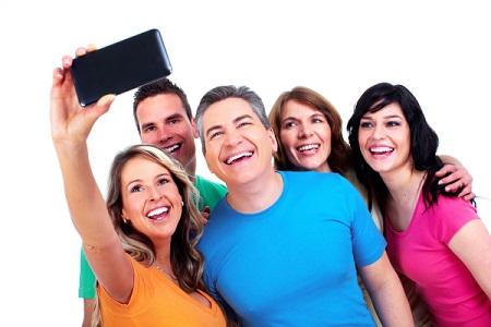 Group of people taking selfie together on camera phone