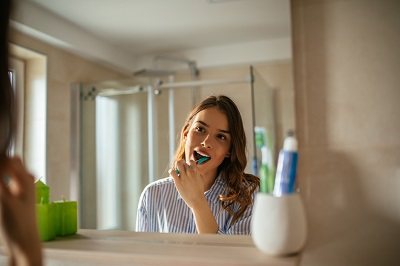 Portrait of a beautiful young woman brushing teeth in the bathroom