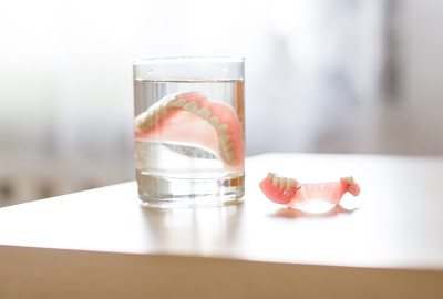 dentures immersed in a glass of water