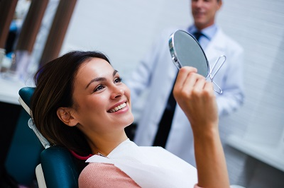Beautiful young woman looking at mirror with smile in dentist's office