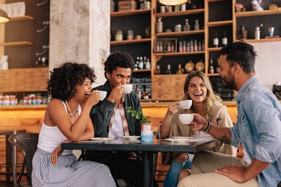 Diverse group of friends enjoying some coffee together in a restaurant and talking.