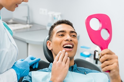 cheerful african american man touching face and looking at mirror in dental chair
