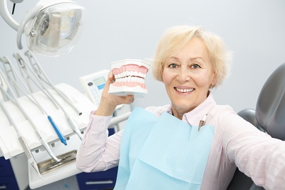 Senior woman smiling joyfully holding a jaw mold sitting in a dental chair