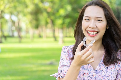 asian woman holding invisalign clear aligner