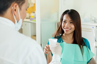 asian woman taking water cup from dental professional