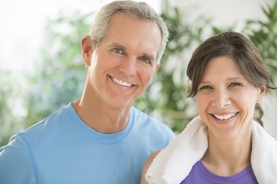 Portrait of fit mature couple smiling outdoors
