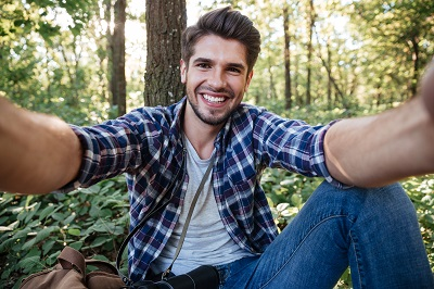 Man sitting and makes selfie in forest. holding camera with two hands.